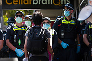 A protestor stands in front of a large group of police during an Extinction Rebellion protest in Melbourne.  A small group of climate protesters marched from Flagstaff Gardens to The Queen Victoria Market and ending with two individuals gluing themselves together, and then glued themselves to Victoria Avenue outside of the Market. This comes as 5 new COVID-19 cases were uncovered in Melbourne's revamped Hotel Quarantine, breaking almost 40 days of virus free days. (Photo by Dave Hewison/Speed Media)