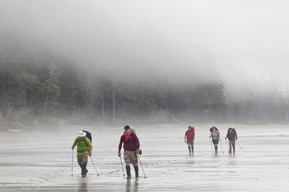 Hikers on a beach in the mist near Bonilla Point, West Coast Trail, British Columbia, Canada.