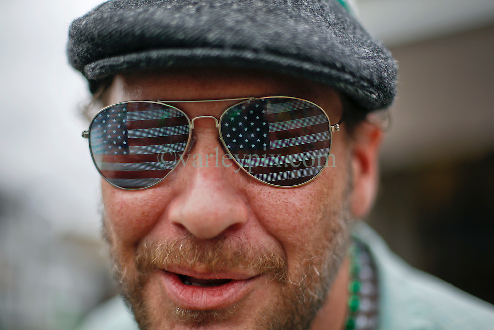 12 March 2016. New Orleans, Louisiana.<br /> Bud at the Irish Channel St Patrick's Day parade as the procession makes its way along Magazine Street.<br /> Photo©; Charlie Varley/varleypix.com