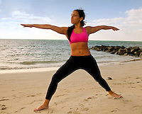 Young woman practices yoga early morning in the beach.