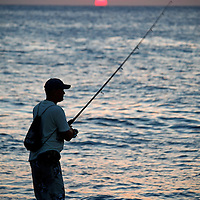 Central America, Cuba, Havana. Fishing on the Malecon at sunset.