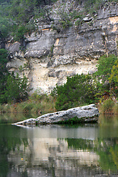 Stock photo of a boulder sticking out from the water in a river in the Texas Hill Country