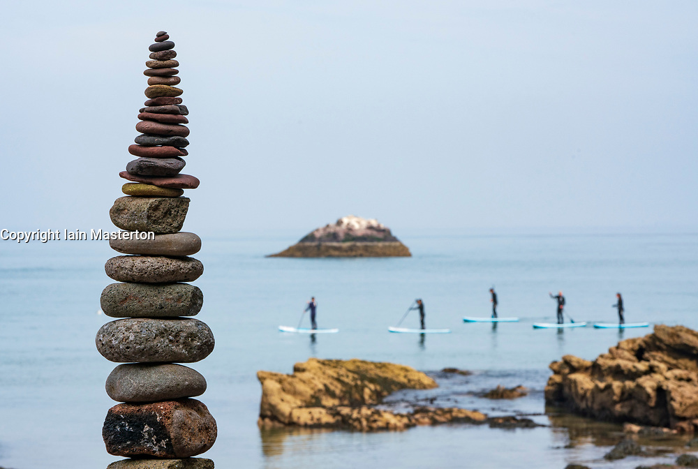 Dunbar, Scotland, UK. 20 April, 2019. Paddle boarders and stone stack at  Eye Cave beach in Dunbar during opening day of the European Stone Stacking Championship 2019.