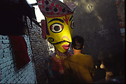 A performer carries a giant puppet through the lanes of Shadipur.Shadipur Depot, New Delhi, India<br /> The Kathiputli Colony in the Shadipur Depot slum is home to hundreds of (originally Rajasthani) performers. The artistes who live here - from magicians, acrobats, musicians, dancers and puppeteers are often international renowed by always return to the Shadipur slum.