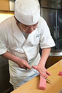 Sushi chef Masatoshi Yoshino is cutting ohtoro saku (fatty tuna) at his restaurant Yoshino Sushi Honten, Tokyo, Japan