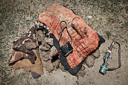 A gun, a horse whip, binoculars and a horse cover thrown over a stack of dry dung, used as fuel in the Pamir. Pamir is localted way above tree line. The summer camp of Kara Jylga, Mullah Abdul Haq place...Trekking through the high altitude plateau of the Little Pamir mountains (average 4200 meters) , where the Afghan Kyrgyz community live all year, on the borders of China, Tajikistan and Pakistan.