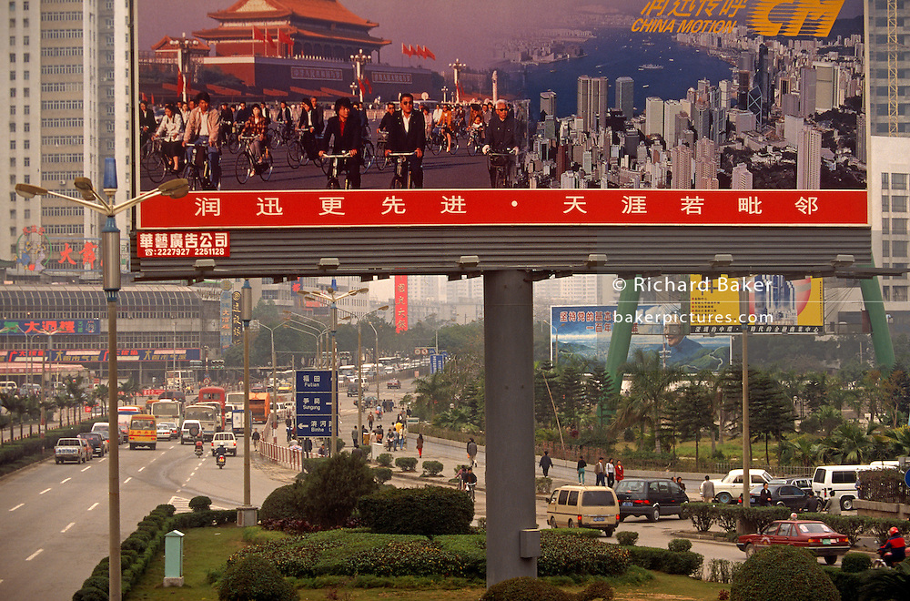 A giant billboard describes the more traditional China - when the main mode of transport was the bicycle and Hong Kong was still a British colony. The reality underneath is a megacity on a scale of a megapolis. Cars pass-by and consumer goods are on ads in the distance. .Shenzhen is a major city in the south of Southern China's Guangdong Province, situated immediately north of Hong Kong. The area became China's first?and one of the most successful?Special Economic Zones (SEZs). It currently also holds sub-provincial administrative status, with powers slightly less than a province. Shenzhen was  named in 2012 as one of the 13 emerging megalopolises in China with a population of 10.3 million.