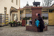 A lady fills a bottle with water from the tap at the main entrance of Rakowicki cemetery in Krakow, Poland in 2019.