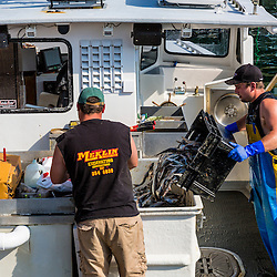 Sternman Jackson Feener (right) and Captain Erick Harjula. loading bait onto Harjula's lobster boat, 'Redeemed' at the Spruce Head Fisherman's Co-op in South Thomaston, Maine.
