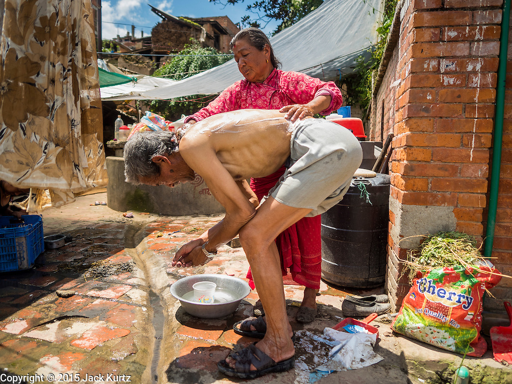 04 AUGUST 2015 - BUNGAMATI, NEPAL: A woman bathes her husband in a small Internal Displaced Persons settlement in the town square in Bungamati, a village about an hour from Kathmandu. Three months after the earthquake many families still live in tents and temporary shelters scattered around the village. The Nepal Earthquake on April 25, 2015, (also known as the Gorkha earthquake) killed more than 9,000 people and injured more than 23,000. It had a magnitude of 7.8. The epicenter was east of the district of Lamjung, and its hypocenter was at a depth of approximately 15km (9.3mi). It was the worst natural disaster to strike Nepal since the 1934 Nepal–Bihar earthquake. The earthquake triggered an avalanche on Mount Everest, killing at least 19. The earthquake also set off an avalanche in the Langtang valley, where 250 people were reported missing. Hundreds of thousands of people were made homeless with entire villages flattened across many districts of the country. Centuries-old buildings were destroyed at UNESCO World Heritage sites in the Kathmandu Valley, including some at the Kathmandu Durbar Square, the Patan Durbar Squar, the Bhaktapur Durbar Square, the Changu Narayan Temple and the Swayambhunath Stupa. Geophysicists and other experts had warned for decades that Nepal was vulnerable to a deadly earthquake, particularly because of its geology, urbanization, and architecture.    PHOTO BY JACK KURTZ