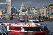 A 'Thames City Cruises' tour boat heads downriver after passing beneath Tower Bridge on the river Thames, on 17th January 2020, in London, England.