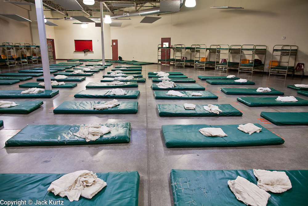 """29 DECEMBER 2010 - PHOENIX, AZ: Overflow beds on the floor wait to be filled at Central Arizona Shelter Services (CASS) in downtown Phoenix Wednesday. Phoenix was hit by a winter storm Wednesday that brought heavy rain and unusually cold temperatures, it is the first day of what is expected to be a week of below normal temperatures. Morning lows by Friday are expected to be 15-20 degrees blow normal. Normal lows for Phoenix are in the 40's but by Friday are expected to be in the 20's. A spokesman for CASS said they expected to fill all of their regular shelter spaces and most of their overflow spaces every night for the next week. In addition to the cold weather CASS has seen demand for the services increase sixfold in the last three years as the Phoenix economy has slid into recession. Many CASS clients now are the """"new"""" homeless - people who used to have homes but lost their homes in the bad economy.      PHOTO BY JACK KURTZ"""