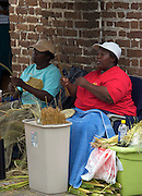 Gullah basket makers weave sweet grass into baskets in historic Charleston, SC. The Gullah, descendants of escaped slaves in South Carolina developed their own traditions and language and made an art form of sweet grass basket weaving.