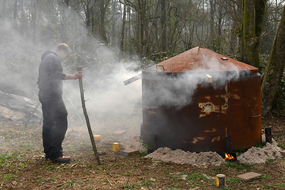 A charcoal kiln being lit in an anchient deciduous woodland in southern England