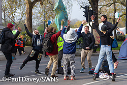 Activists dance in the early morning light on Oxford Street as hundreds of environmental protesters from Extinction Rebellion occupy Marble Arch, camping in the square and even on the streets, blocking access to traffic on Park Lane and Oxford Street in London's usually traffic-heavy west end. . London, April 16 2019.