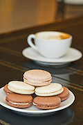 A stack of macaroons next to a cup of coffee at Meridienne Dessert Salon and Cafe in Rogers, Arkansas.