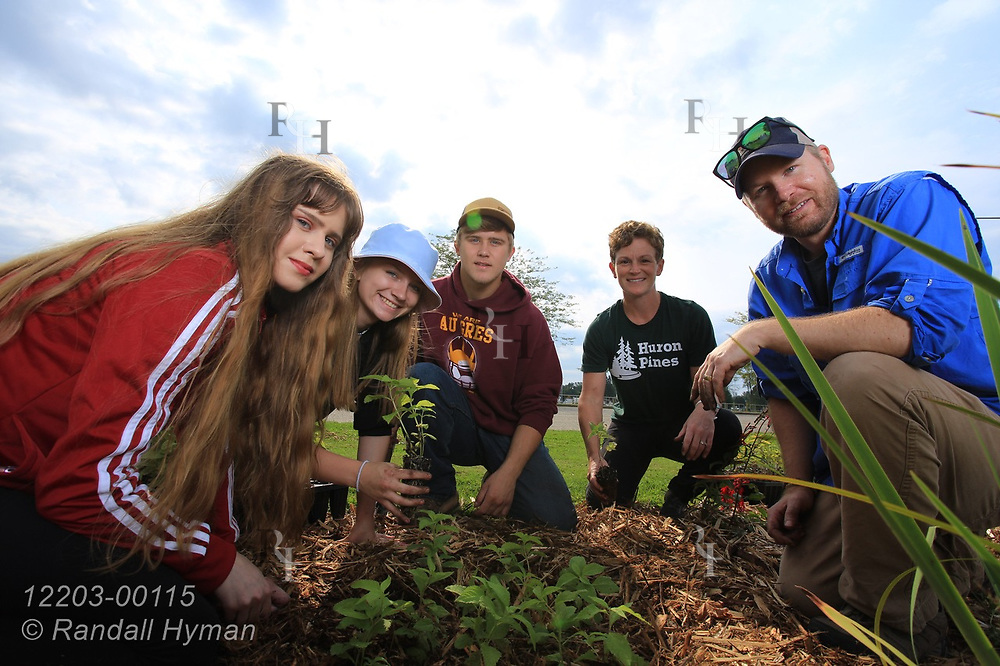 High school environmental sciences students pose with teacher Luke Freeman and Huron Pines community program director Abby Ertel while planting wildflowers in bioswale of rain garden at River Side Park in Au Gres, Michigan.