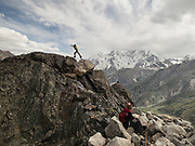 A young trekker jumps over rocks in the Hindukush, near the Darkot pass (4690m).
