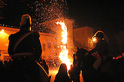 The General on his horse are looking at the burning Scarlo, a large pole covered by heather and juniper in Ivrea, pop. 30.000. During the days of the Carnival, Ivrea becomes crammed with tourists coming to witness the event which finds its roots at the end of the XII Century, when the people led an insurrection against the local tyrant, Count Ranieri of Biandrate, who was exercising the 'jus primae noctis' rule (having the first night) on the local young brides. The battle to overthrow him is represented with a 3-day-fight between factions in which more then 400 tonnes of oranges are thrown. During the celebrations, food stalls, bands playing music, and parades are also present, giving it a typical Medieval atmosphere. .