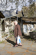 Greece, Epirus, Zagororia, Megalo Papigko villages, located in the Vikos-Aoos National Park, local woman in the street