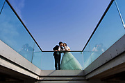 An Asian newlywed couple pose for a morning photoshoot on Millennium Bridge on the 27th August 2018 in Central London in the United Kingdom.