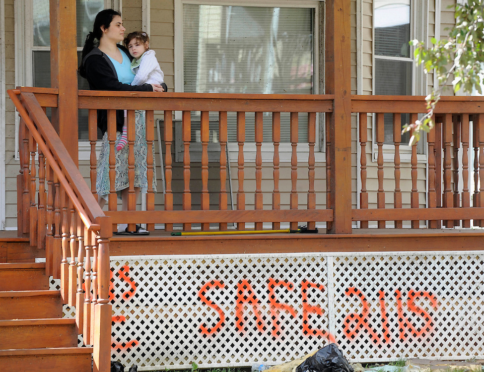 Aziza Radzhabova holds her daughter Salvi, 4, on the porch of their home a day a tornado in West Springfield, Mass., Thursday, June 2, 2011.  Radzhabova and her family was home the day of the tornado and said they had no warning their neighborhood was in the tornardo's path. (AP Photo/Jessica Hill)