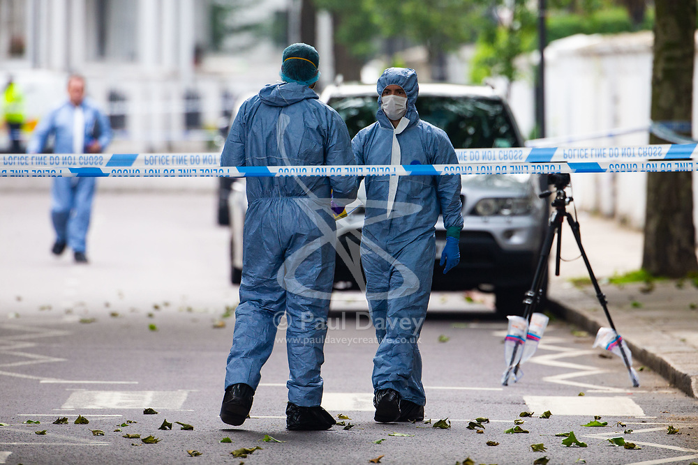 Forensics investigators collect evidence at the scene outside a block of flats at 65 Finborough Road, adjoining Cathcart Road, Chelsea following the fatal stabbing on the night of May 30th 2018 of a man in his forties, said to be a delivery driver who refused to hand over his cash to robbers. London, May 31 2018.