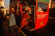A lady passenger leaps on to the rear board of a red London Routemaster bus on a 1990s street, on 18th February 1992, in London, England.