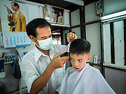 27 JUNE 2015 - BANGKOK, THAILAND:   A barber cuts a boy's hair in the Bang Luang neighborhood of the Thonburi section of Bangkok. The Bang Luang neighborhood lines Khlong (Canal) Bang Luang in the Thonburi section of Bangkok on the west side of Chao Phraya River. It was established in the late 18th Century by King Taksin the Great after the Burmese sacked the Siamese capital of Ayutthaya. The neighborhood, like most of Thonburi, is relatively undeveloped and still criss crossed by the canals which once made Bangkok famous. It's now a popular day trip from central Bangkok and offers a glimpse into what the city used to be like.       PHOTO BY JACK KURTZ
