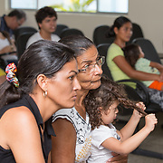 CAPTION: Maria is a joyful and spirited little girl. Here, she is seen playing with her curls as she sits on her grandmother Maria's lap while she and her mother Rosana listen carefully to the doctors who'll soon be reviewing her cleft correction surgery, five months after her operation. LOCATION: Hospital Geral de Benjamin Constant, Rua 13 de Maio, 1496, Benjamin Constant, Amazonas, Brazil. INDIVIDUAL(S) PHOTOGRAPHED: From left to right: Rosana de Souza, Maria Souza and Maria Souza.