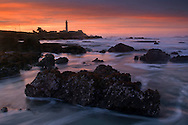 Clouds at surnise over waves and coastal rocks at low tide at Pigeon Point Lighthouse, San Mateo County coast, California
