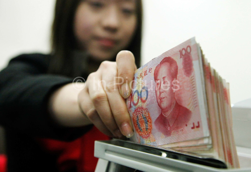 An HSBC employee counts Chinese Renminbi (RMB) notes at the bank's newly opened 100th China branch in Shanghai, China, on 09 June, 2010. To the worry of China's exporters, the Chinese currency has steadily appreciated against other major world currencies abolishing its peg system to the United States Dollar.