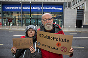 Paid to Pollute claimants Kairin van Sweeden and Jeremy Cox outside the Department for Business, Energy and Industrial Strategy on 2nd October 2021 in London, United Kingdom. Kairin and Jeremy are two of the three climate activists taking the UK government to court over the billions of pounds of public money it spends supporting the oil and gas industry, as part of the Paid to Pollute campaign. <br /> <br /> Jeremy Cox is a retired former oil worker, current Extinction Rebellion activist, beekeeper, green woodworker and amateur baker.<br /> <br /> Kairin van Sweeden is an SNP Common Weal organiser for the North east of Scotland, the daughter of an oil worker, an Aberdeen quine and Executive Director of the Modern Money Scotland think tank.