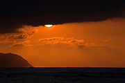 An image of the sun peaking down below a cloud at sunset at the North Shore of Oahu, Hawaii.