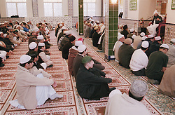 Worshippers inside mosque listening to preacher,