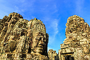"02 JULY 2013 - ANGKOR WAT, SIEM REAP, SIEM REAP, CAMBODIA:  Stone heads in Bayon, one of the temples in the Angkor Wat complex. Angkor Wat is the largest temple complex in the world. The temple was built by the Khmer King Suryavarman II in the early 12th century in Yasodharapura (present-day Angkor), the capital of the Khmer Empire, as his state temple and eventual mausoleum. Angkor Wat was dedicated to Vishnu. It is the best-preserved temple at the site, and has remained a religious centre since its foundation – first Hindu, then Buddhist. The temple is at the top of the high classical style of Khmer architecture. It is a symbol of Cambodia, appearing on the national flag, and it is the country's prime attraction for visitors. The temple is admired for the architecture, the extensive bas-reliefs, and for the numerous devatas adorning its walls. The modern name, Angkor Wat, means ""Temple City"" or ""City of Temples"" in Khmer; Angkor, meaning ""city"" or ""capital city"", is a vernacular form of the word nokor, which comes from the Sanskrit word nagara. Wat is the Khmer word for ""temple grounds"", derived from the Pali word ""vatta."" Prior to this time the temple was known as Preah Pisnulok, after the posthumous title of its founder. It is also the name of complex of temples, which includes Bayon and Preah Khan, in the vicinity. It is by far the most visited tourist attraction in Cambodia. More than half of all tourists to Cambodia visit Angkor.         PHOTO BY JACK KURTZ"