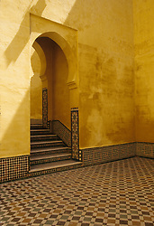 Africa, Morocco, Meknes, courtyard of Moulay Ismail Mausoleum, with yellow walls and mosaic tile floor