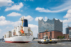 View of new Elbphilharmonie concert hall and cargo ship on River Elbe in Hamburg Germany