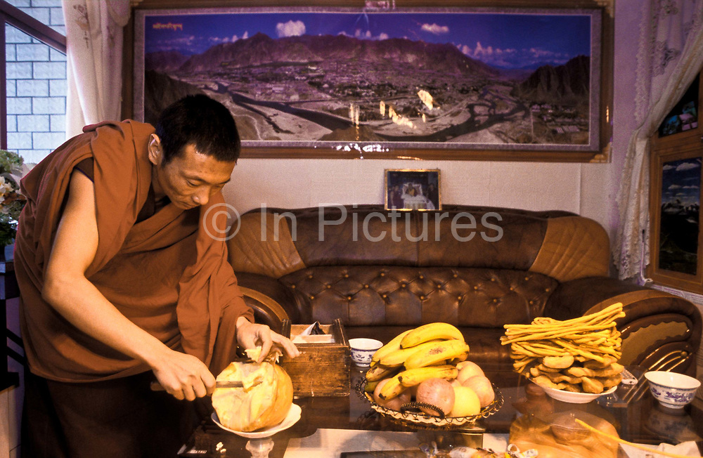 Tibetan buddhist monk Dongyu, preparing and eating breakfast comprising of hot water mixed with barley and Yak butter  to make a high energy paste known as Tsampa in his small but well furnished living space (living room / bedroom) in 300 years old Atsog Monastery, Xinghai County, Qinghai Province, China.