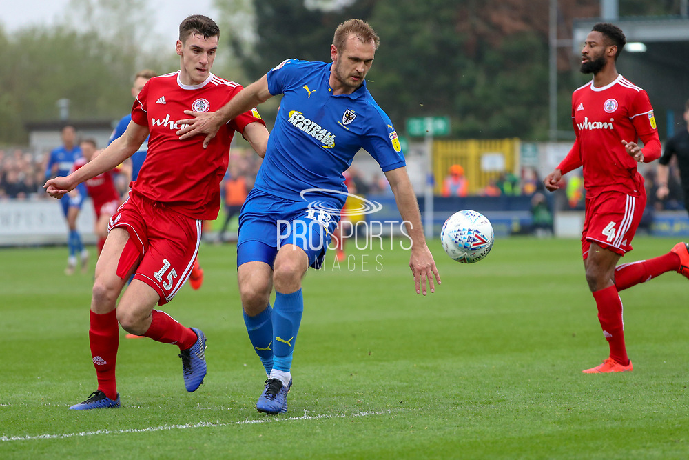AFC Wimbledon striker James Hanson (18) battles for possession with Accrington Stanley defender Ross Sykes (15) during the EFL Sky Bet League 1 match between AFC Wimbledon and Accrington Stanley at the Cherry Red Records Stadium, Kingston, England on 6 April 2019.