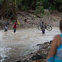 After the double hurricanes of Eta and Iota, people cross the Quebrada El Calan. Massive damage was caused along the waterway after the hurricanes.