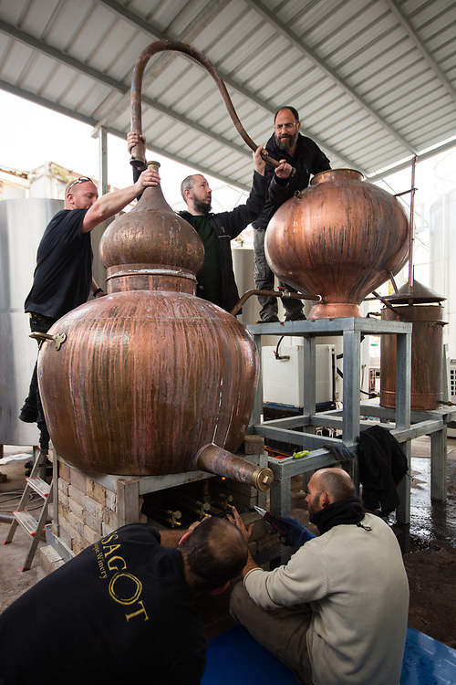 Jewish Israeli workers are seen as they set up a copper pot still which will be used to distill brandy, at Psagot Winery in the West Bank Jewish settlement of Migron, near the Palestinian West Bank city of Ramallah, on November 17, 2015.