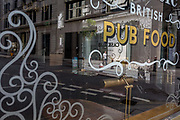 With the Coronavirus lockdown continuing into the Bank Holiday weekend, when Prime Minister Boris Johnson is due to tell the nation that only a gradual easing of regulations and social distancing rules are still to be in place, a cyclist is the only form of life seen through the window of a closed British pub in a deserted City of London, the capitals financial district, on 7th May 2020, in London, England.