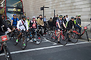 Cyclists waiting at traffic lights in the City of London. Cycling has become a very popular mode of transport in the capital as people try to avoid public transport, saving money, getting fit and saving time.