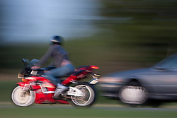 Motorcycle and car on a freeway duel it out for position on the roadway