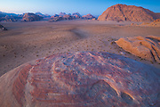 Pink sandstone formations and distant mountains at dusk in Wadi Rum, Jordan.