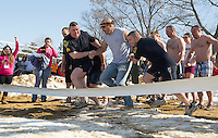 """Sgt Gary Hubbard (Left) and Patrolman Ben Black (right) take their """"fugitive"""" Chief Christopher Adams into Lake Winnipesaukee for the annual Winni Dip for Special Olympics on Sunday afternoon at the Margate Resort.  (Karen Bobotas/for the Laconia Daily Sun)"""