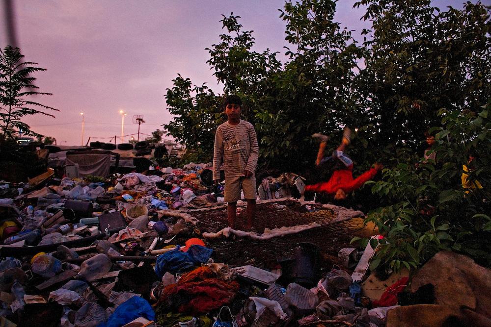Boys play on top of a garbage pile behind their home in Nova Gazela.