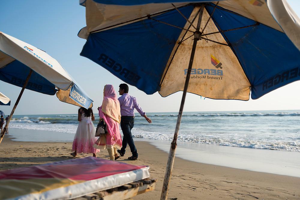 Cox's Bazar, Bangladesh - October 27, 2017: A family walks at the beach in Cox's Bazar, Bangladesh