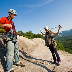 A couple prepares to go rock climbing at the top of Cathedral Ledge.  Echo Lake State Park in North Conway, New Hampshire.  White Mountains.